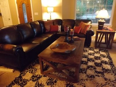The living room has a leather couch with a cozy big rug and 55in Smart TV.