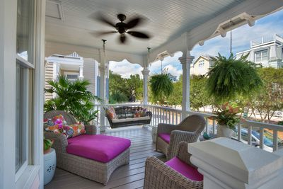 inviting front porch with comfortable wicker furniture and cooling ceiling fan.