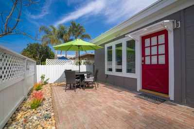 Front of house with landscaped patio, table, chairs and umbrella.