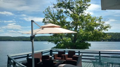 Large deck overlooking the lake w/ plenty of furniture and  cantilever umbrella
