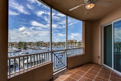 The screened porch offers breathtaking views of the water and boats.
