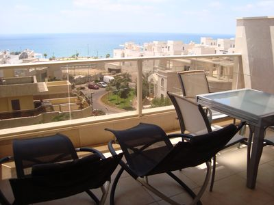 Balcony with 2 lounge chairs and table. Enjoy beautiful scenery with meals.