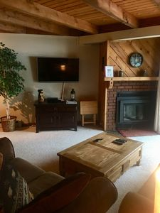 Another view of the living room area with gas fireplace and flatscreen TV.