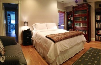bedroom and sitting room - The thoughtfully decorated and furnished main room features a queen bed, night stands, loveseat, writing desk, wall mounted TV, full length mirror, closet, luggage rack, and a second exit.