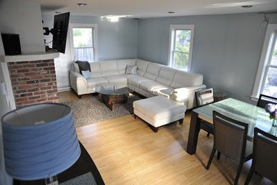 Open living room & dining room. 55' HDTV with stereo, blu ray & WI-FI.
