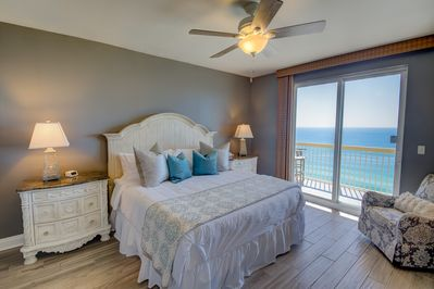 King beach bedroom with patio door to deck, blackout curtains.