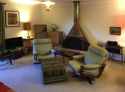 Cosy lounge with 70's classic copper hooded open fireplace