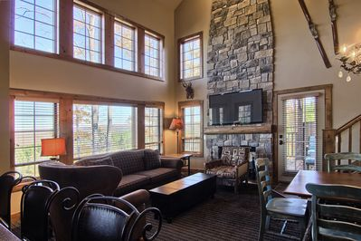 Cozy living room with beautiful floor to ceiling windows and cus - Cozy living room with beautiful floor to ceiling windows and custom stone fireplace