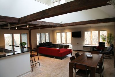 New, white pickled parquet floors look up to loft, many skylights.