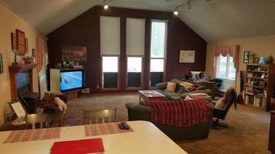 Great room off of kitchen with large screen TV and woodburning stove.