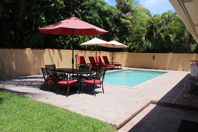 Heated pool with chaise lounges and umbrellas.