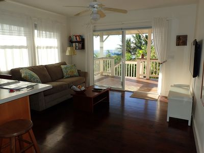 Living room opens on covered deck with ocean