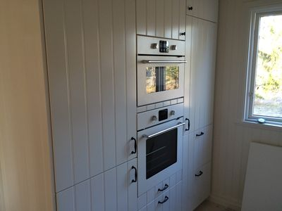 Kitchen with oven, microwave, dishwasher, freezer, glass cooktop etc