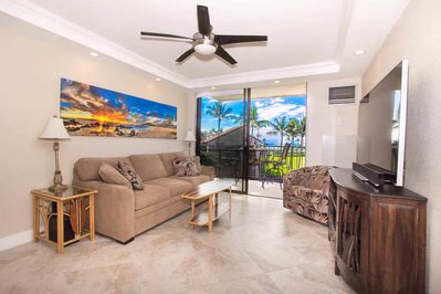 Living room with tan couch, flat screen TV, and mounted beach art
