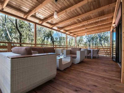 Photo for Modern chalet featuring a spacious veranda with garden lounge set, on a park by the sea