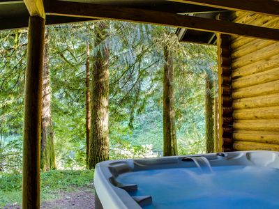 Photo for Spacious, riverfront lodge with beach access, private hot tub & forest views!