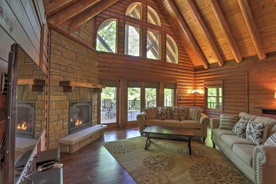 Rustic wood beams and floor-to-ceiling windows highlight the interior.