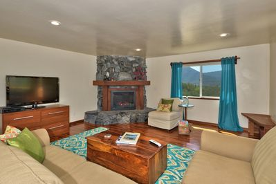 Inviting living room with ample seating, big-screen TV and electric fireplace.