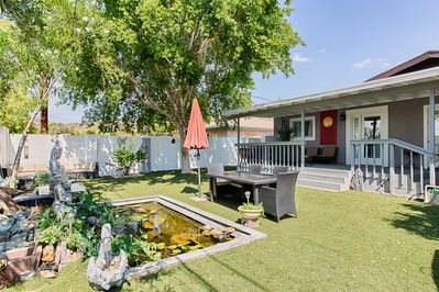 Large yard with koi pond, fountain and huge shade tree