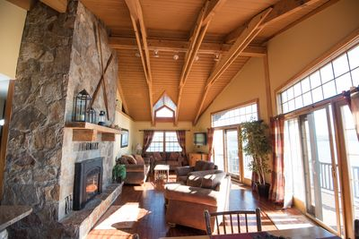 Livingroom with natural stone fireplace and panoramic views of the lake!