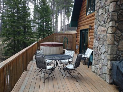 Large front deck with hot tub, gas grill and outdoor seating.