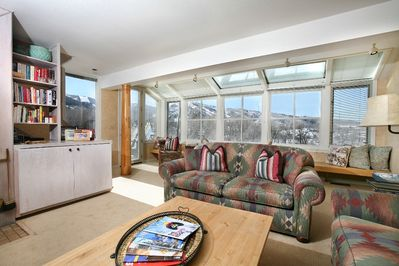 The big living/great room with panoramic views, door to deck and hot tub