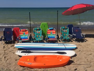 Beach chairs, umbrella, boogie boards, surfboard, SUP and kids kayak for summer.