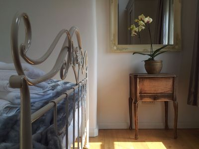 Sunny romantic bedroom with oak floors and a Laura Ashley king size bed