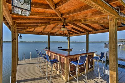 Featuring a long dock and bar, this home is the perfect summer getaway.