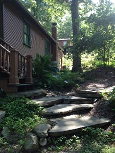 Front porch steps meet natural stone down to the lake