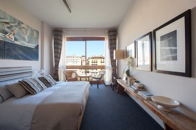 Bedroom with full wall window overlooking Arno river