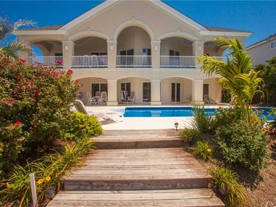 Photo for Elegant 8 bedroom home on the bay with private dock & pool, in-home theater, short walk to the beach