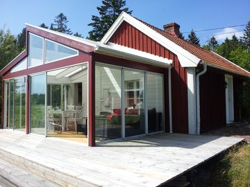 Family friendly red Sweden house, right by the sea between forest and meadow