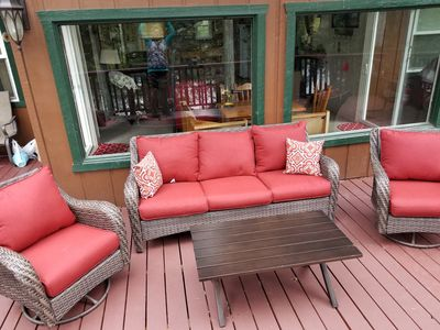 Enjoy the deck and the water view with cushioned couch and oversize wicker chair