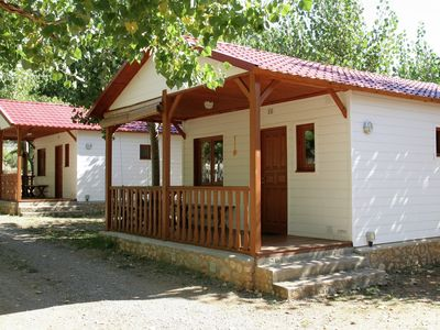 Photo for Wooden bungalow located on a small holiday park with a swimming pool in a beautiful environment.