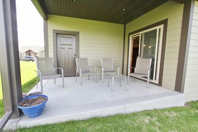 Back porch has four chairs and comes off the dining room