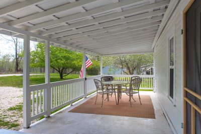The front porch welcomes you with a table and 4 chairs.