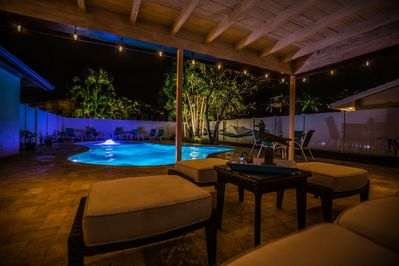 Patio accent lighting creates a cozy tropical backyard at night!