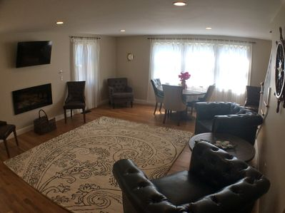 Living / Dining area, table with seating for 6, two leather chairs, flat tv