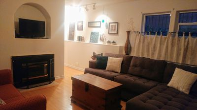 Living area with bay window, chaise, pull out love seat and gas fireplace/ TV.