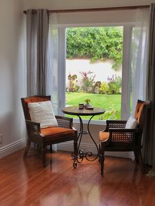 Big plush chairs where you can sit, view the garden oasis thru big bay windows.