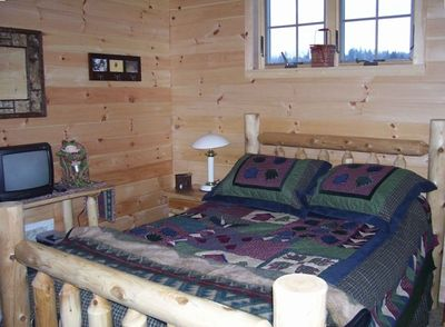 Cozy master bedroom with log furnishings