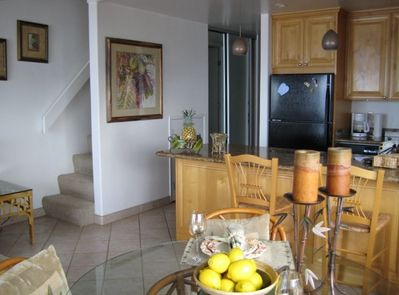 Cozy dining area, stairs to loft & granite countertops in kitchen.