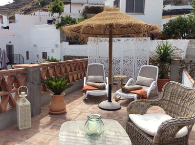 Roof terrace and sun loungers . Terrace views down to the sea and mountains .
