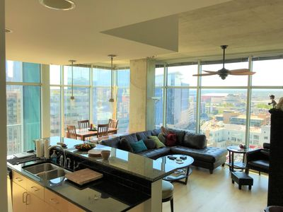 Family room  and dining areas with floor to ceiling glass walls.