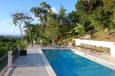 Palashia Villa pool with view of ocean and tropical gardens around