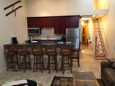 kitchen, bar stools and stair that lead to the 2 bedrooms upstairs