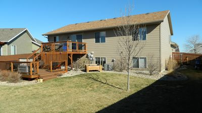 Back of house with upper and large lower deck, gas grill.