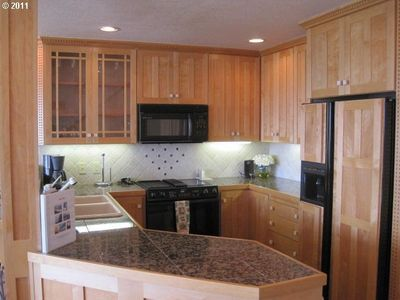 Open kitchen with warm cabinets and granite counters.