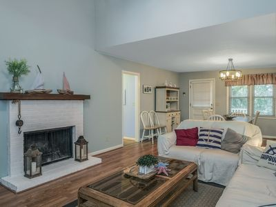 The living room has cathedral ceilings and hardwood floors, an HDTV and sliding doors leading to the screened in porch.
